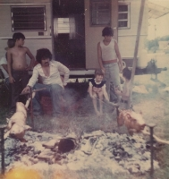 The Leo Johns family roasts a couple of young pigs. Marie Rivera and Johnny Johns turn the spits. Myers Amusements. 1970's.jpg