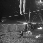 nina-leen-two-small-children-watching-circus-performer-practicing-on-tightrope-her-legs-only-visible.jpg
